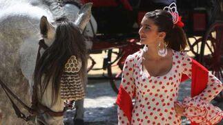 Cruce de miradas entre un caballista y una flamenca.  Foto: José Ángel García