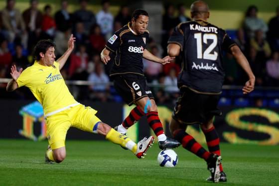 Kanoute observa cómo Adriano se hace con el balón pese a la entrada de su rival.  Foto: LOF, EFE