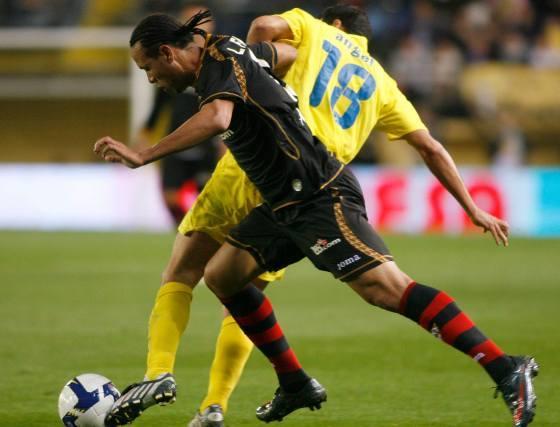 Luis Fabiano se cae al suelo ante una jugada de Ángel por arrebatarle el esférico.  Foto: LOF, EFE