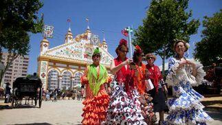 Varias mujeres vestids de gitanas pasean por el real.  Foto: José Ángel García
