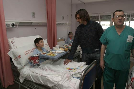 Visita del Sevilla F.C. a los niños de la Planta Infantil del Hospital Virgen Macarena, a los que repartieron regalos. Javi Navarro charla con un niño.   Foto: Jaime Martínez