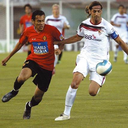 El capitán Sevilla FC, Javi Navarro disputa el balón al jugador del RCD Mallorca, Juan Arango, durante el partido perteneciente al Campeonato de Liga , en el Ono Estadi de la capital balear.   Foto: Montserrat T. Díaz (Efe)