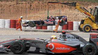 En primer plano, Lewis Hamilton. Al fondo, la grúa se lleva el coche de Bourdais.  Foto: Reuters / AFP Photo / EFE