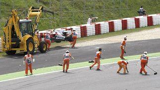 La grúa se lleva el coche de Trulli mientras los operarios limpian la pista.  Foto: Reuters / AFP Photo / EFE