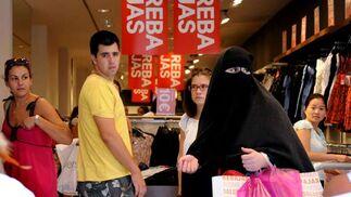 varias personas miran a una mujer cubierta con un burka que también aprovechaba las rebajas para hacer sus compras.  Foto: Juan Carlos Vázquez