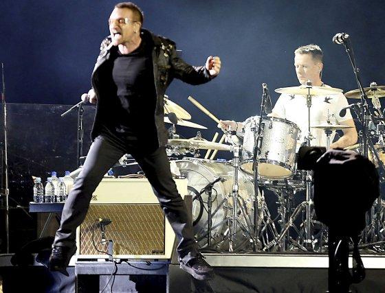 Bono salta delante de Larry Mullen, batería de U2.  Foto: EFE