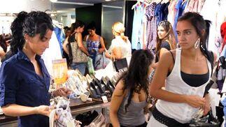 Varias jóvenes ojean algunas prendas en una conocida tienda de ropa del centro de Sevilla.  Foto: Juan Carlos Vázquez