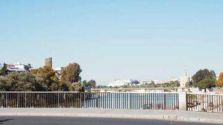 Imagen virtual de la Torre Cajasol asomando entre los árboles desde el Puente de Los Remedios.