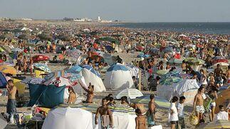 Unos que llegan, otros que se van. Bañistas y asistentes a la barbacoa coincidieron sobre la arena.  Foto: Lourdes de Vicente