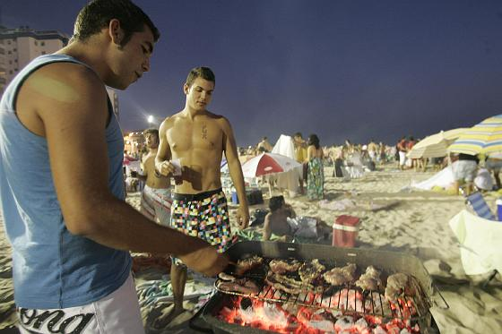 Unos jóvenes preparan la cena en la arena.   Foto: Lourdes de Vicente