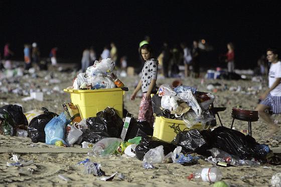Una joven observa el estado de los bidones de basura.   Foto: Lourdes de Vicente