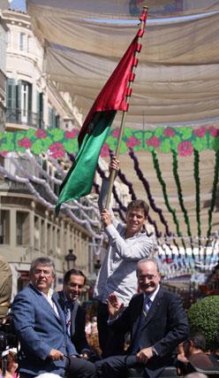 Javier Ojeda, el abanderado de la feria, en un carruaje junto con el Alcalde de Málaga, el Concejal de Cultura y el Presidente de la Asociación del Centro Histórico,iza la bandera de Málaga en la Plaza del Marqués de Larios. FOTO: Migue Fernández
