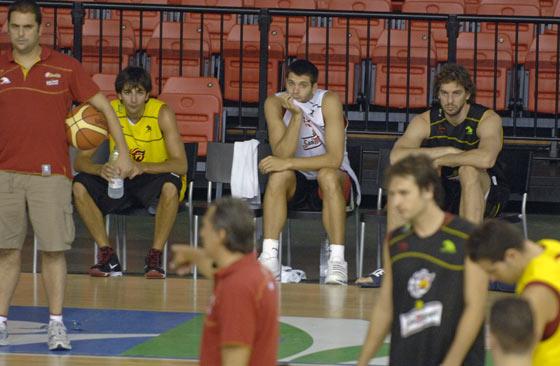 Ricky Rubio, Felipe Reyes y Pau Gasol observan, desde el banquillo, a sus compañeros de equipo./ Manuel Gómez