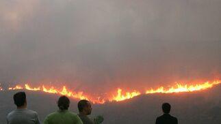 Hombres observan el fuego a 15 kilómetros de Atenas.  Foto: Efe