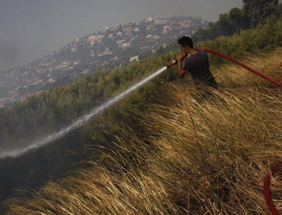 Un voluntario combate las llamas en la población griega de Pedeli, a 20 kilómetros de Atenas.  Foto: Efe