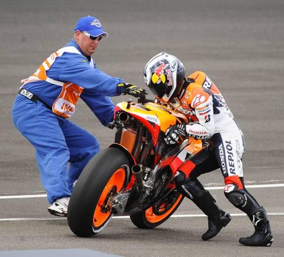 Dani Pedrosa levanta su motocicleta con ayuda de un juez de pista.