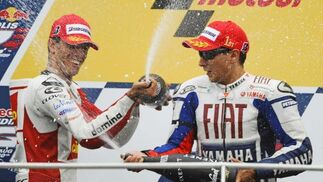 El español Jorge Lorenzo celebra su victoria con Alex De Angelix, que quedó en segundo lugar.