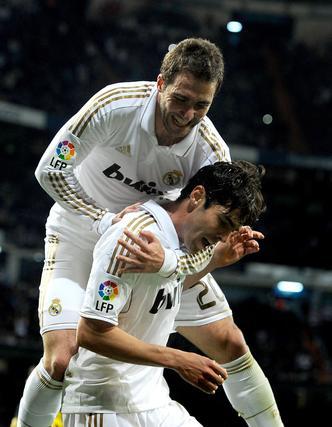 Higuaín salta sobre Kaká en la celebración del cuarto gol madridista. / AFP