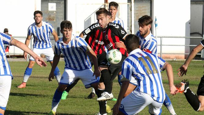 Misffut, Víctor y Alberto Barrero, del Recreativo B, intentan que un jugador del Cabecense no se lleve la pelota.