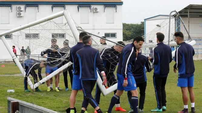 Los jugadores del Decano colocan una portería sobre el césped en un entrenamiento reciente.
