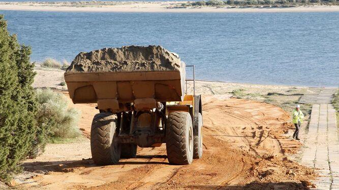Una retroexcavadora transporta arena de la zona de acopio de Nuevo Portil.