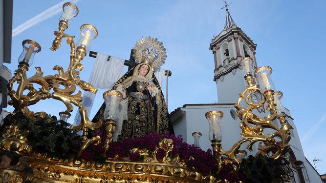 Nuestra Señora en su Soledad en la salida de la procesión con la parroquia de la Purísima Concepción de fondo.