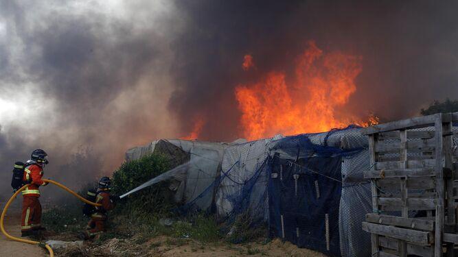Un bombero lucha contra las llamas que se cebaron en los materiales inflamables del asentamiento.