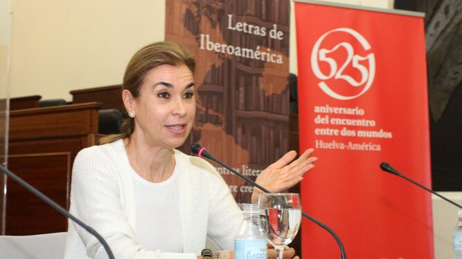 La escritora Carmen Posadas, en un momento de su intervención. En la imagen superior, a su llegada al salón seguida por Lucía Vallellano.