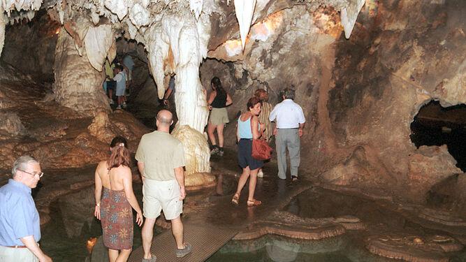 Un grupo de visitantes realiza el recorrido por el interior de la Gruta de las Maravillas, entre estalactitas y estalagmitas.