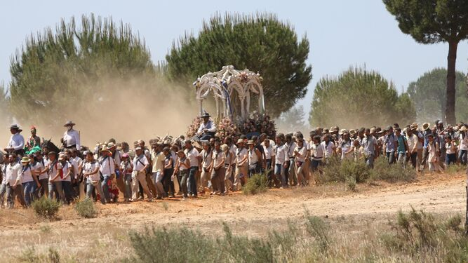 El Simpecado de la Hermandad de Huelva camina rodeado de peregrinos hacia la aldea para reunirse con la Blanca Paloma.