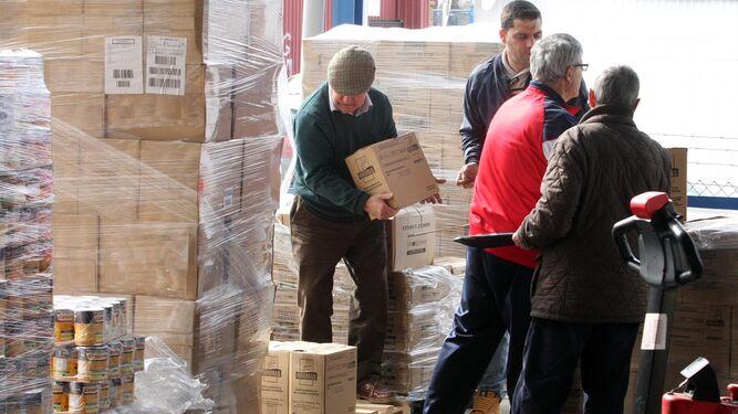 Trabajos de selección de los paquetes de productos alimenticios en la nave que el Banco de Alimentos tiene en la capital onubense.