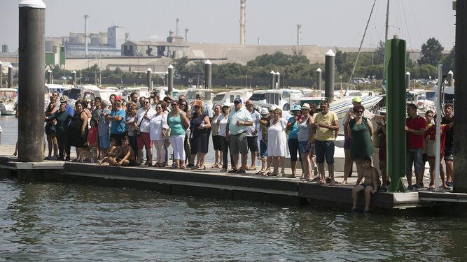 El muelle del Real Club Marítimo de Huelva se llenó de devotos en el momento de la ofrenda.