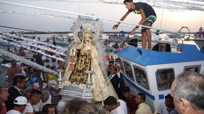 La Virgen del Carmen es subida a una embarcación para la procesión en Isla Cristina.