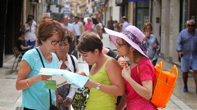 Unas turistas miran el plano de la ciudad de Huelva.