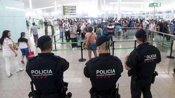 Los mossos vigilan una de los accesos a las puertas de embarque de El Prat.