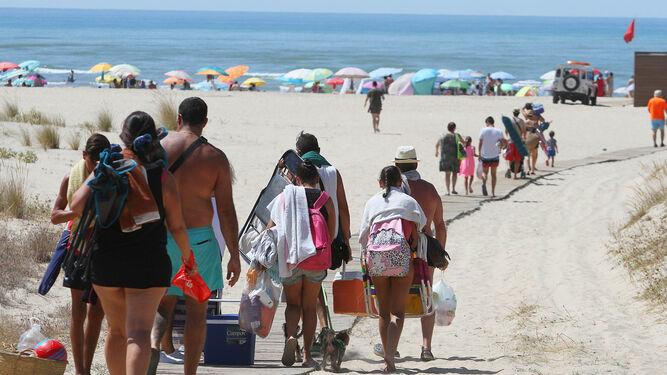 Personas caminan por la pasarela en El Cruce. Aspecto que presentaban ayer Punta Umbría y Matalascañas.