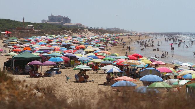 Las sombrillas multicolores cubren totalmente la playa en la localidad de Punta Umbría, en la zona de Las Conchas.