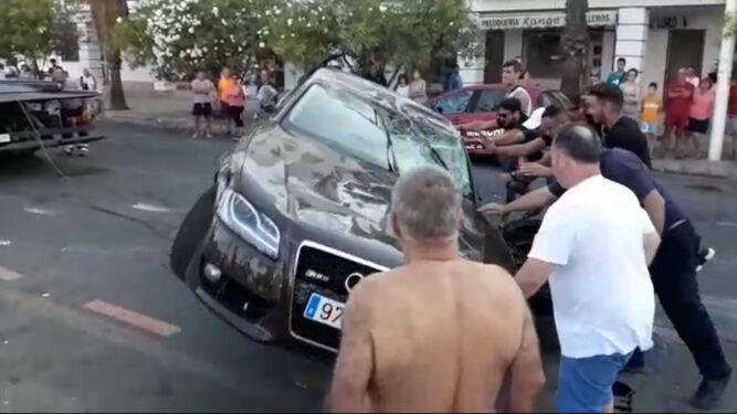 Varios hombres empujan el coche hasta apoyarlo sobre las ruedas.