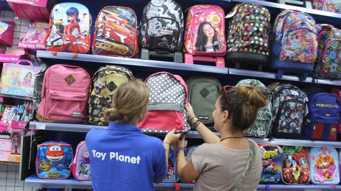 2 Escolar Empleada Atiende Mujer Tienda Variedad Equipamiento Gran En Toy Una De Planet Fútbol Equipos Mochilas Sección La A Pd4ZZqw