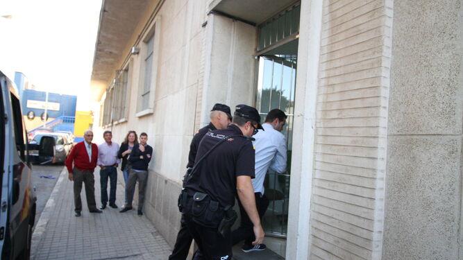 Los padres y el hermano del acusado (al fondo) ven entrar a Medina en el Palacio de Justicia escoltado por dos agentes, ayer.
