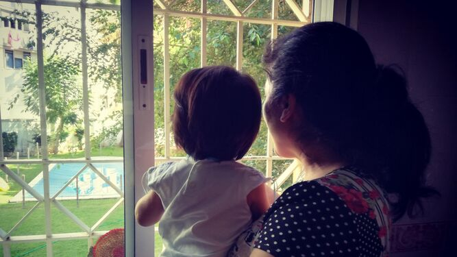 Una joven con su pequeño miran a través de la ventana.