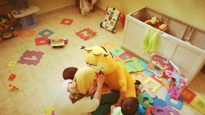 Una madre juega con sus dos hijos en una de las habitaciones de la Casa Familia Oasis.