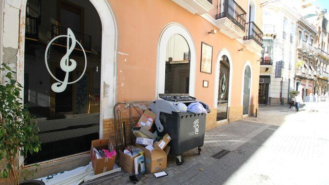 Contenedor lleno de basura, con cajas amontonadas en uno de sus laterales, ayer al mediodía, en la céntrica calle Rico.