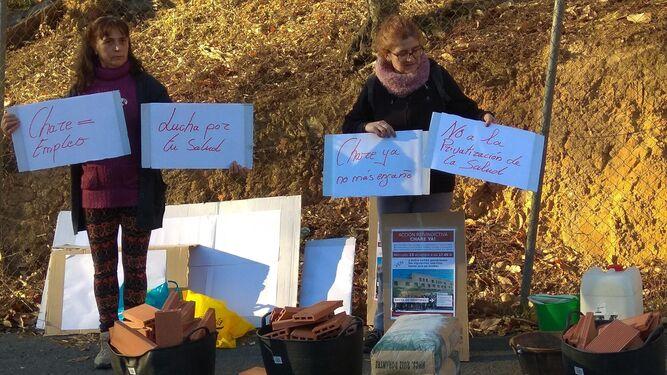Dos mujeres muestran los carteles que reclaman el reinicio de las obras.