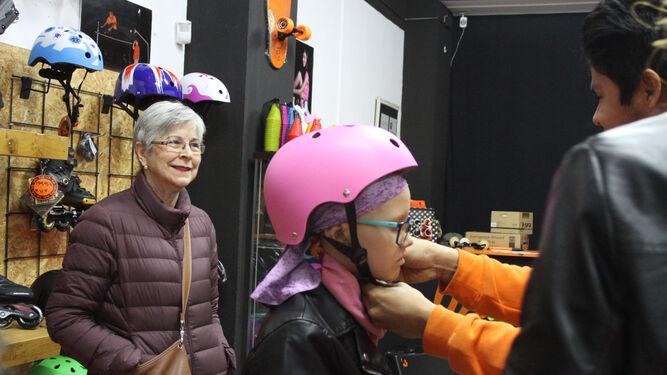 Un monitor coloca el casco rosa a la pequeña en la tienda.