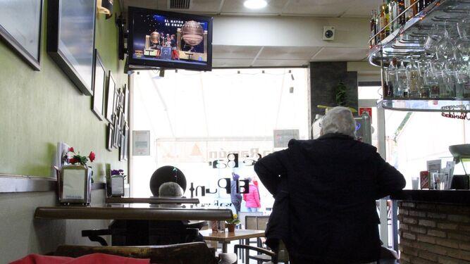 Un hombre apoyado en la barra de bar sigue el Sorteo de Navidad.