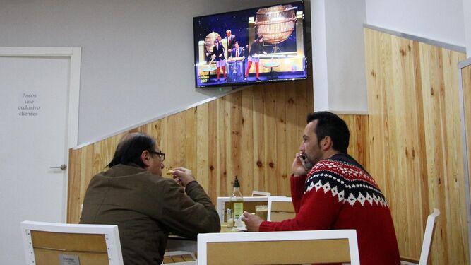 Dos hombres charlan en un bar con la lotería de fondo en el televisor.