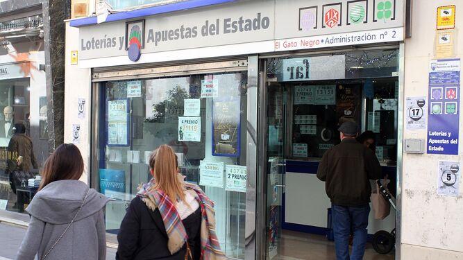 Dos jóvenes pasan por la puerta de la administración El Gato Negro de Huelva, ayer.