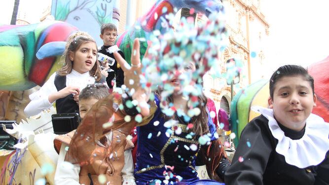 Una niña arroja un puñado de papelillos a la cámara.