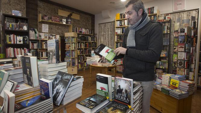 Manuel Jesús Soriano muestra un ejemplar de 'Patria', el libro del año, en el interior de su librería, La Dama Culta, en la calle Cardenal Cisneros.